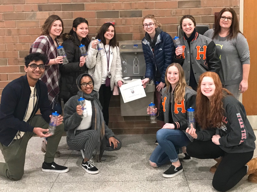 Hoover science teacher Mrs. Sarah Covington poses with the Hoover Aultman Ambassadors in front of the hydration station, which was a result of a grant and is located near Hoover Hall.