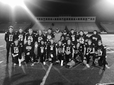 The senior boys football team poses with Coach Baum after a game.